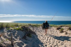 18604120 - cape cod, ma - june 19, 2010: woman going fishing at race point beach, cape cod.
