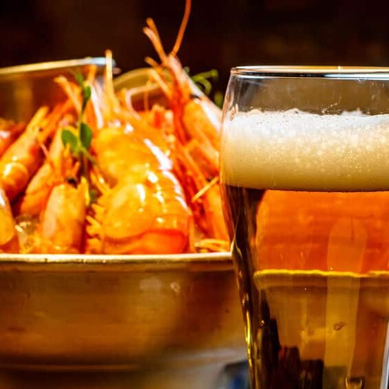 A glass of beer in the background is a plate of crab, shrimp, sc