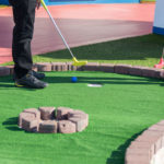 A man prepares to hit a ball during a mini golf game